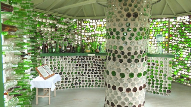 Intérieur d'une maison de bouteilles, avec une colonne au centre et un livre d'or sur une table.