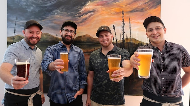 Quatre jeunes hommes tiennent des bières.