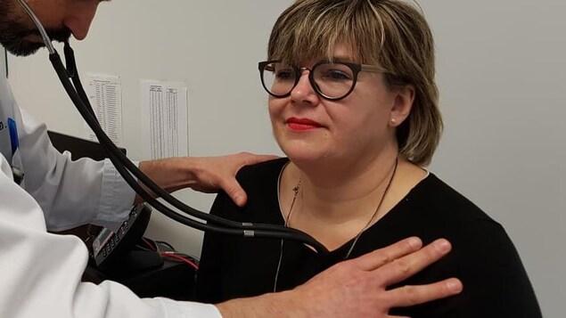Un médecin écoute le battement de cœur d'une patiente grâce à son stéthoscope.