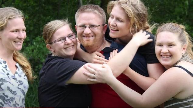 Samuel Brandt souriant entouré des ses soeurs.