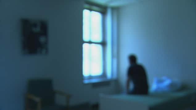 Un patient d'un hôpital assis sur un lit regardant par la fenêtre.