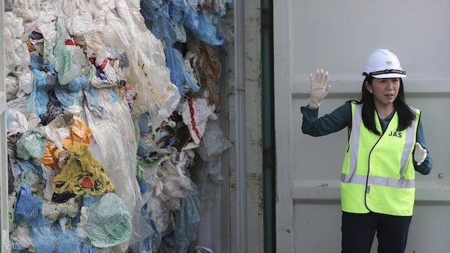 Une femme parle aux journalistes devant un conteneur rempli de sacs de plastique.