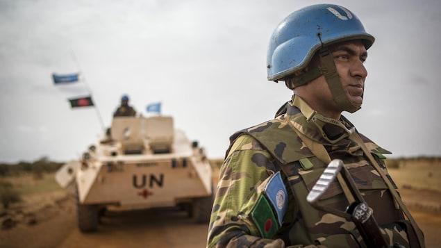 Un soldat de l'ONU, portant son casque bleu et son fusil, fixe l'horizon en se tenant bien droit devant un tank de l'ONU, au Mali.
