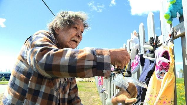 Tabi McKenzie devant la clôture du site Innu Nikamu à Mani-utenam.