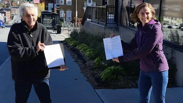 Jacques Malouin et Christine Labrie tiennent chacun une copie de la pétition en se tenant à distance l'un de l'autre.