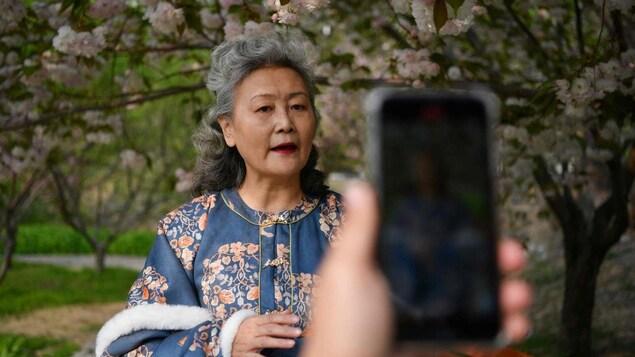 Une femme dans un parc avec des arbres en fleur parle devant un téléphone cellulaire qui la filme.