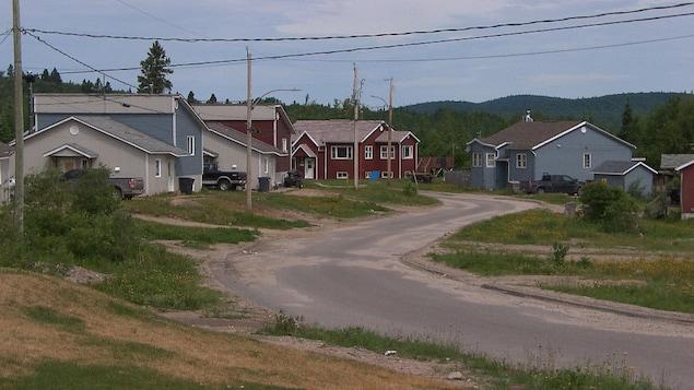 Des maisons rouges et bleues sont vues aux abords d'une route. Elles semblent être situées en banlieue ou en campagne.