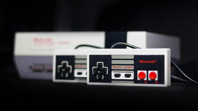 Deux manettes NES devant une console NES.