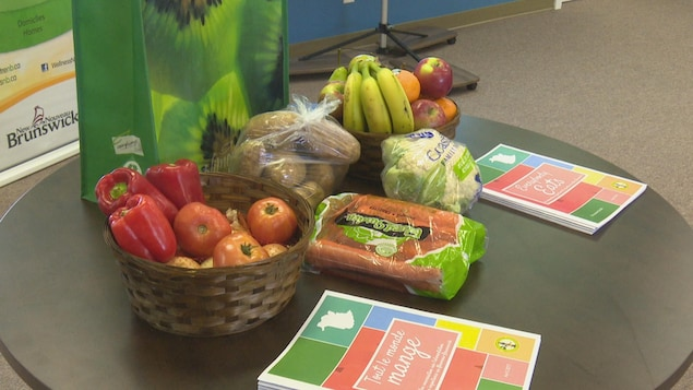 Une table sur laquelle des légumes et des fruits frais sont disposés : poivrons, tomates, bananes, pommes, carottes, oranges, chou-fleur.