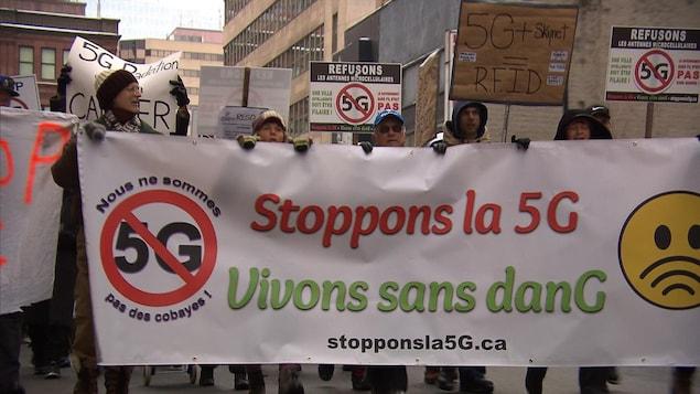 Une bannière sur laquelle est inscrit: Stoppons la 5G  est tenue par plusieurs manifestants.