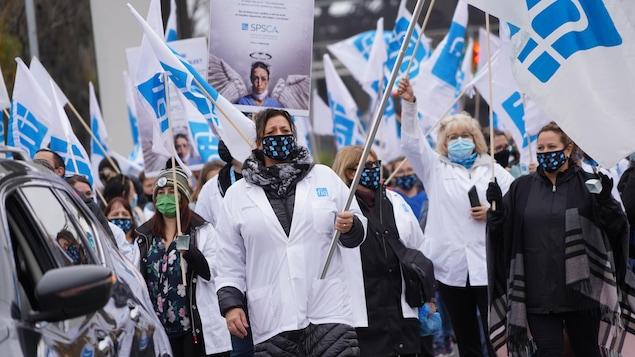 Des infirmières défilent dans la rue en brandissant des drapeaux.