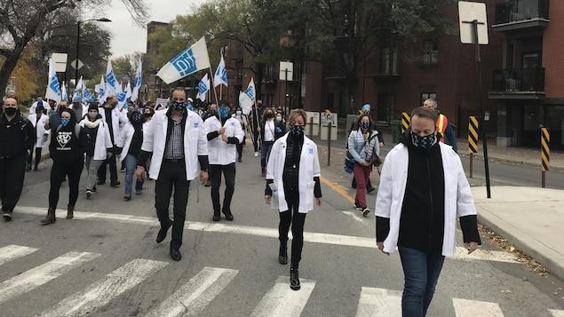 Des syndiqués en sarrau défilent dans la rue.
