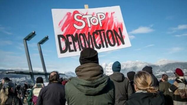 Un manifestant tient une pancarte lors d'un rassemblement pour les logements à Vancouver en février.