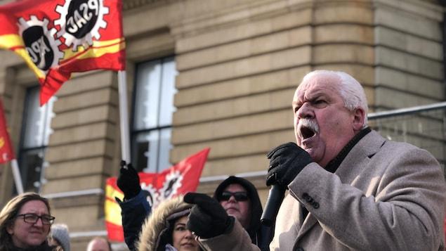 Chris Aylward parle au microphone lors d'une manifestation dehors en hiver à Ottawa.