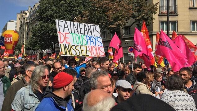 Un manifestant brandit une pancarte indiquant «Fainéants de tous les pays, unissez-vous!»