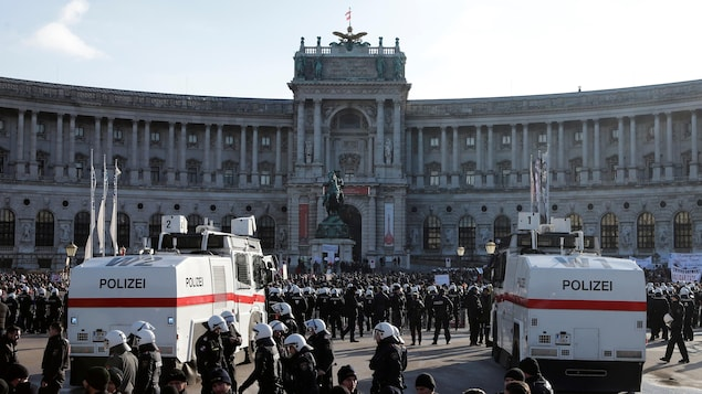 Des policiers se déploient devant des manifestants.