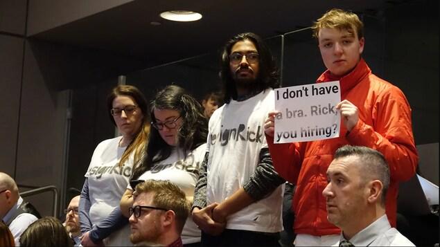 Des manifestants à l'hôtel de ville d'Ottawa, l'un d'eux montre une affiche où il est écrit : « Je n'ai pas de soutien-gorge Rick, est-ce que tu embauches ?»