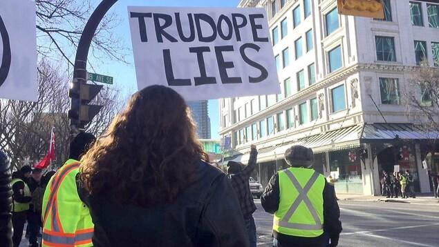 Des manifestants propipeline portant des gilets jaunes brandissent des pancartes devant l'hôtel de ville à Calgary.