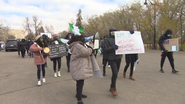 Une dizaine de manifestants brandissant des pancartes à dénoncent la violence policière au Nigeria lors d'une marche à Regina