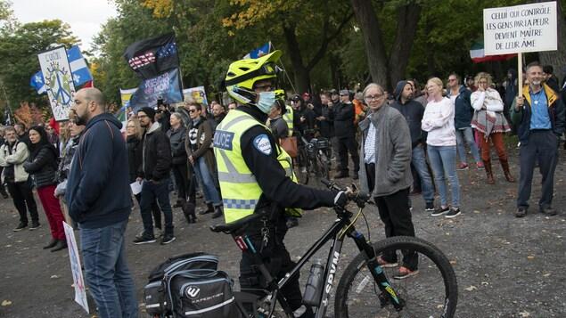 Un policier à vélo et qui porte un masque, au milieu de manifestants qui protestent contre le port obligatoire du masque.