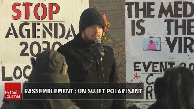 Un homme prend la parole à l'extérieur avec un micro.