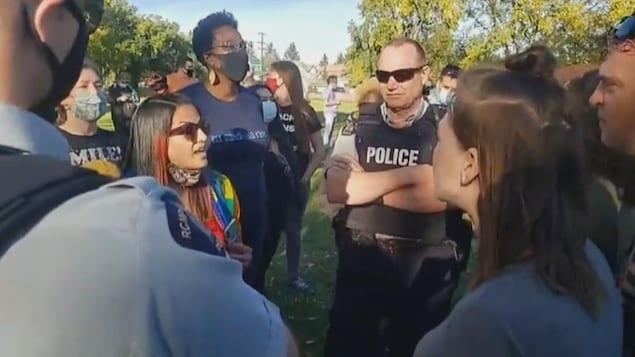 Plusieurs hommes et femmes se lancent des insultes devant deux policiers impassibles.