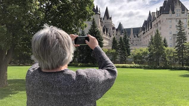 Un femme de dos à la caméra prend une photo du Château Laurier avec son téléphone intelligent.