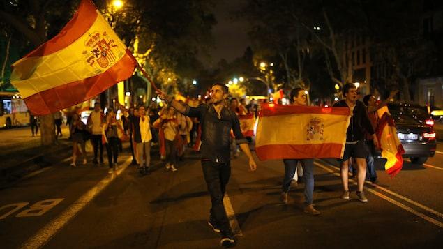 Des manifestants, opposés à l'indépendance de la Catalogne, brandissent des drapeaux de l'Espagne dans Barcelone, le mercredi 4 octobre 2017.