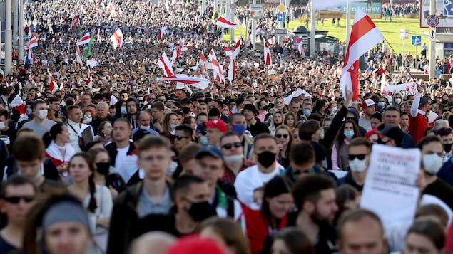 Une foule immense marche avec des drapeaux.