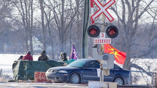 Une voiture et une barricade avec des manifestants sont installées sur la voie ferrée.