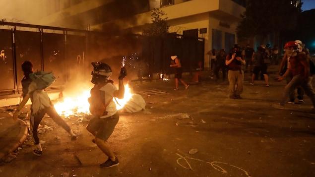 Les manifestants sont devant un petit incendie dans la rue.