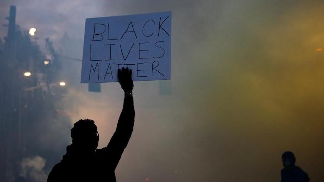 Un homme, de dos, brandit une pancarte sur laquelle il est écrit: « Black Lives Matter » dans un nuage de gaz lacrymogène.