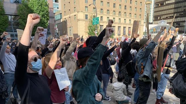Des manifestants, la plupart masqués, lèvent le poing.