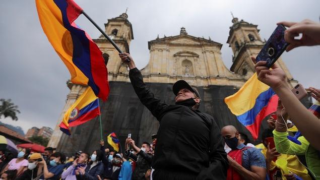 Une femme brandit un drapeau colombien dans la rue.