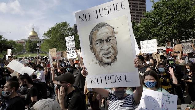 Au milieu d'une foule nombreuse, une jeune femme tient une pancarte sur laquelle on peut voir une illustration de George Floyd avec les mots « Pas de justice, pas de paix » lors d'une manifestation contre la brutalité policière à Boston.