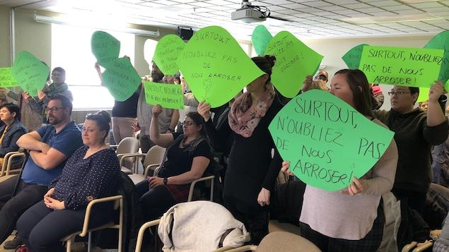 Des travailleuses et des bénévoles tiennent des pancartes en forme de feuilles vertes sur lesquelles on peut lire : « Surtout, n'oubliez pas de nous arroser ».