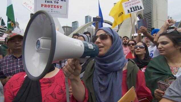 Un femme tient un mégaphone dans une manifestation