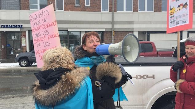 Des manifestantes, dont une avec un porte-voix.