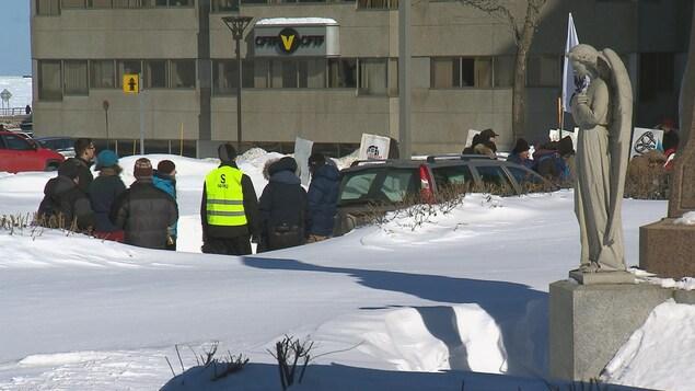 Des manifestants bordent une route devant l'église de Rimouski.