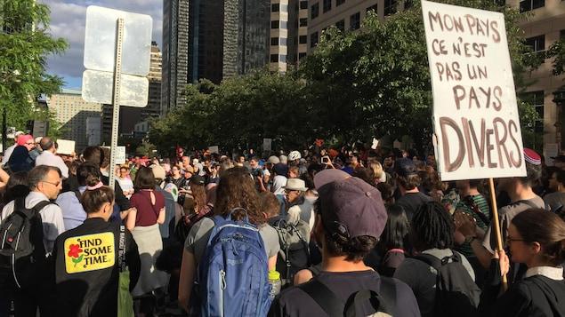Une foule rassemblée sur la rue à Montréal; l'une des personnes porte une pancarte où l'on peut lire : « Mon pays, ce n'est pas un pays divers ».