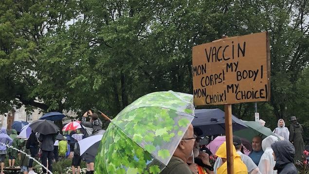 Un manifestant brandissant une affiche contre le vaccin.