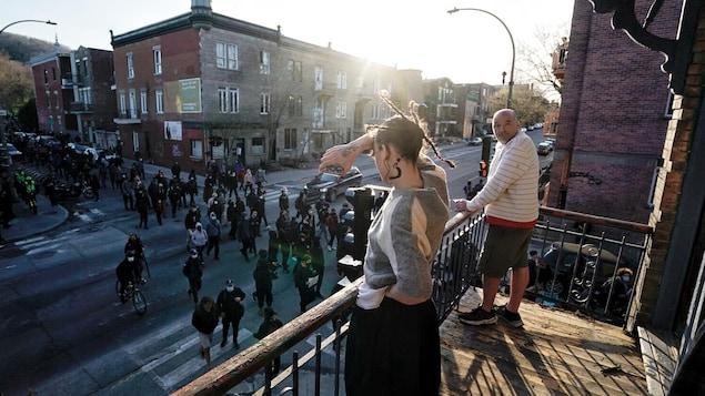 Des résidents observent les manifestants de leur balcon.