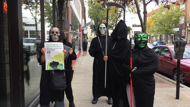 Cinq personnes tiennent une faux, sont habillées en noir et portent un masque.