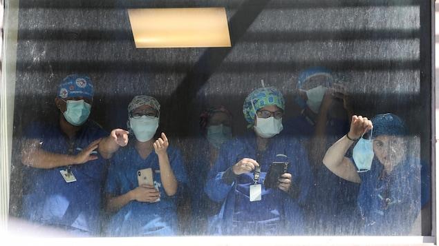Photographié de la rue, un groupe de travailleuses et travailleurs de la santé rassemblés devant une fenêtre de l'hôpital.
