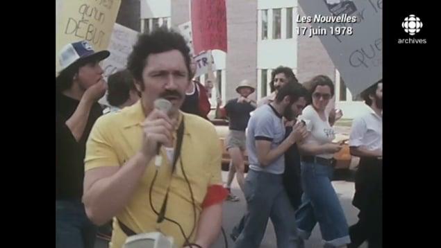 Un homme dans la manifestation tient un micro. À l'arrière, d'autres manifestants marchent.