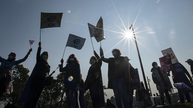 Des manifestants avec des pancartes à contre jour.
