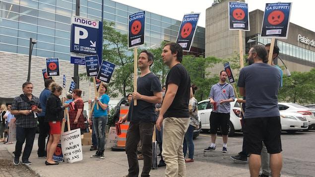 Un groupe d'employés de La Presse et Nuglif manifeste devant le parc de La Presse, à Montréal, alors qu'on voit le Palais des congrès en arrière-plan.