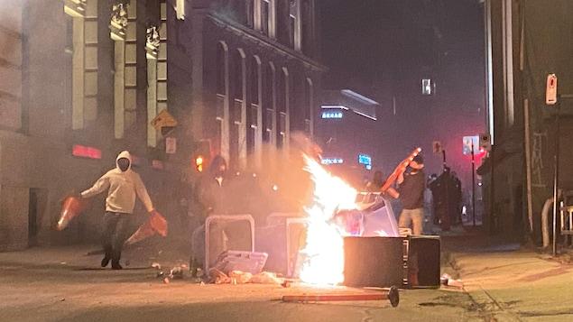 Des manifestants devant des objets en flammes.