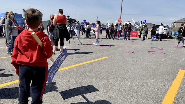Un enfant de dos qui tient une pancarte avec des intervenantes en petite enfance en arrière-plan.