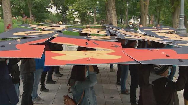 Les manifestants tiennent des pancartes au-dessus de leurs têtes.